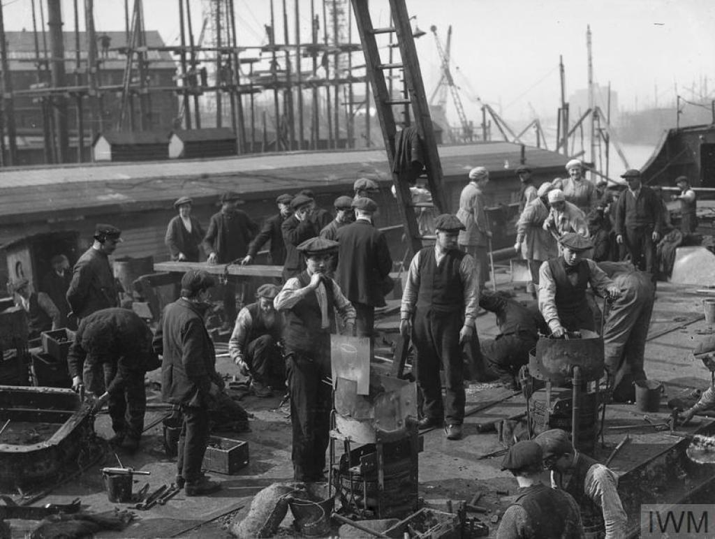 © IWM (Q 20002) Workers beginning on the ship 'skeleton', which can be seen in the background, at Harland and Wolff shipbuilding yard, Clydebrae Street, Govan, Glasgow.