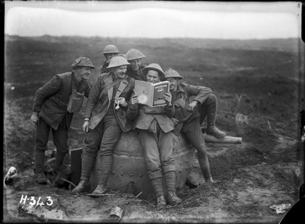 World War I New Zealand soldiers with a copy of 'New Zealand at the Front'. Royal New Zealand Returned and Services' Association :New Zealand official negatives, World War 1914-1918. Ref: 1/2-012980-G. Alexander Turnbull Library, Wellington, New Zealand. /records/22539048