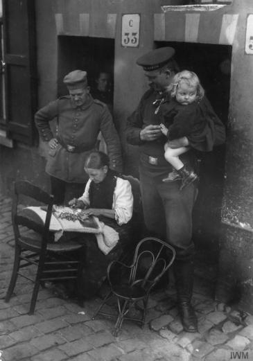 German soldiers watching a female lacemaker at work in German occupied Belgium
