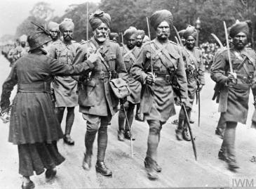 During a march past of Indian troops, a woman pins flowers on to the tunic of one of the soldiers. © IWM (Q 70214)