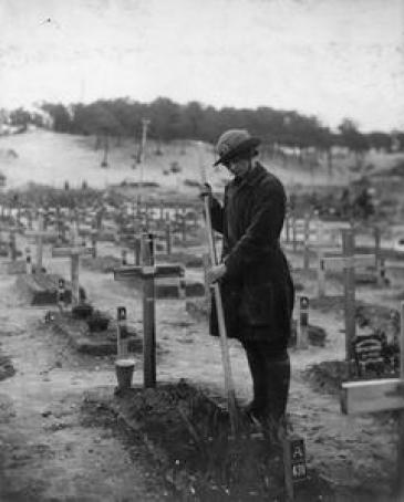 The grave of Betty Stevenson is tended to by a member of the Women's Army Auxiliary Corps (WAAC) in a graveyard at Etaples, France.