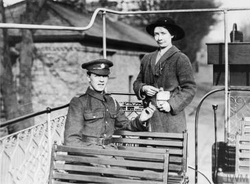 A female tram conductor of the LUR Tramway Company issues a ticket to a British soldier on an open top tram. © IWM (Q 109772)